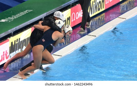 Gwangju, South Korea - July 26, 2019. U.S. team players jump into the pool with head coach Adam Krikorian as celebrate their victory over Spain in the final at the FINA Waterpolo World Championship.
