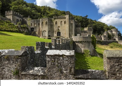Gwrych castle in Wales UK surrounded by trees and foliage on hill side ruins