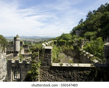 Gwrych castle in Wales UK surrounded by trees and foliage on hill side ruins in summer