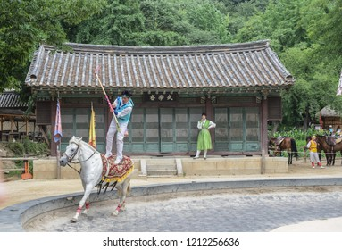 Gyeonggi-do, S. Korea - July 05, 2015: Performance by stuntman dressed in traditional Hanbok as a warrior standing on top of a running horse in Korea.