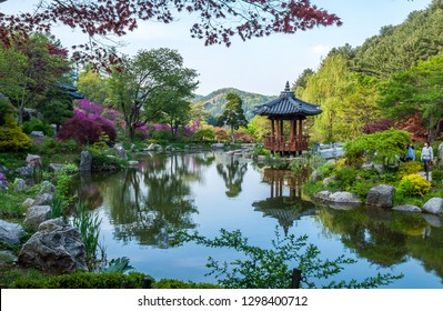 """GYEONGGI-DO, SOUTH KOREA - APRIL 29: Landscape photo of a beautiful Korean-style garden pond in the """"Garden of Morning Calm"""", with a Korean-style pavilion on the edge of the pond."""