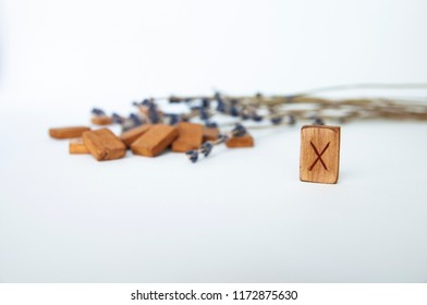 Gyfu. Scandinavian runes. Wooden runes on a table on a white background.