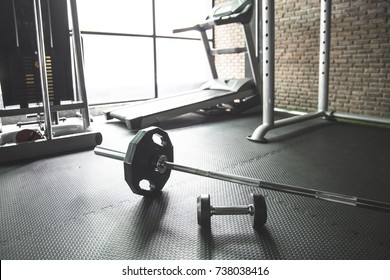 Gym background with barbell dumbbell on the empty floor.Fitness equipment for weight training or CrossFit.