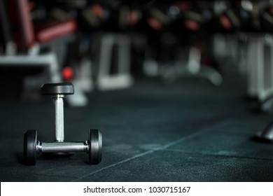 Gym background with Dumbbells on dark floor with free copy space
