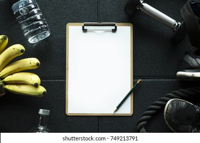 Gym background with Mockup clipboard note plan for the workout.Detail with healthy food banana and water and fitness equipment
