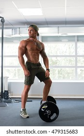 At gym. Bodybuilder poses with his foot on barbell