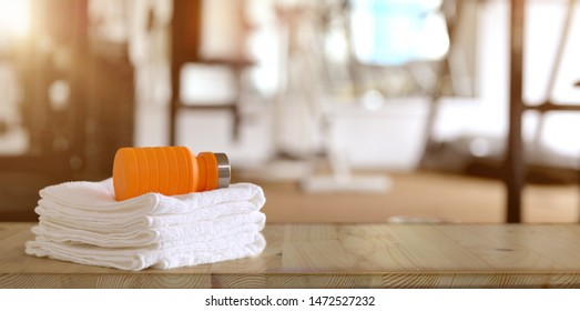 Gym concept : Towels and orange sport bottle with gym background