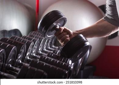 Gym equipment, hand holding dumbbell. Sport background.