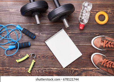 Gym equipment, notebook with copy space. Be healthy and strong with physical exercises.