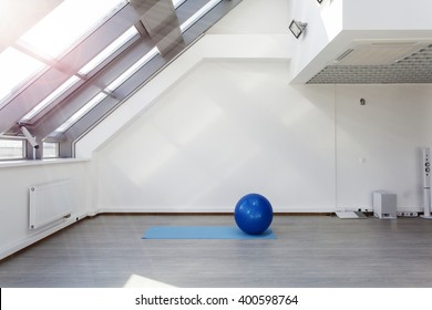 Gym for fitness exercises. Fitball and mat  lie on the floor. The room is flooded with daylight sunlight from the window, the glare on the white wall. Audio system with speakers in the background.