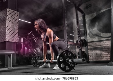 In the gym, the girl does exercises for the development of the muscles of the legs and back.