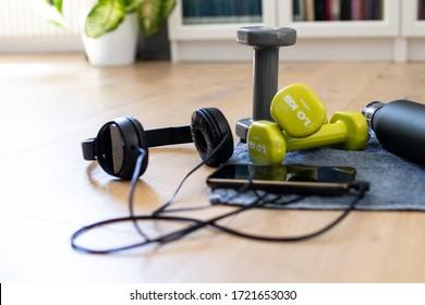 Fitnessraum zu Hause, Fitnesszubehör zu Hause. Instrumente für sportliche Aktivitäten: Handtuch, Kopfhörer, Handy, Hantel und Wassertank. Einrichtung für Schulungsmaßnahmen zu Hause. Filterfarben und Vintage-Farben
