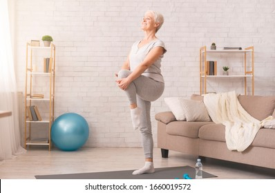 Gym at home. Active senior woman doing legs exercise at home, empty space