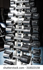 gym indoor interior with steel chromized dumbbells; vertical  photo