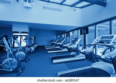 gym interior with equipment and row of jogging simulators, monochromatic