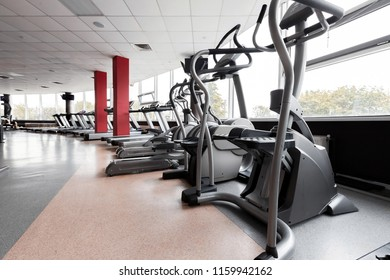 Gym interior with modern equipment. light modern room with row of elliptical trainers. concept of sport and healthy lifestyle