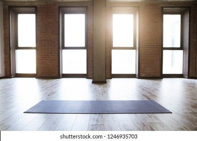 Gym loft interior with blue yoga mat, big windows and sunlight, no people. Copy space