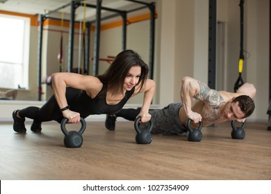 Gym man and woman push-up strength pushup with kettlebells in a fitness workout