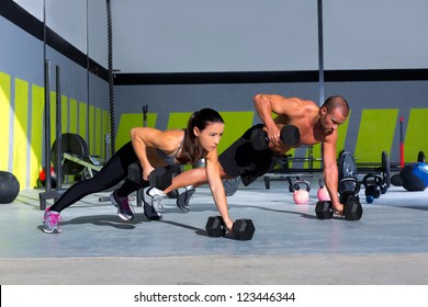Gym man and woman push-up strength pushup with dumbbell in a fitness workout