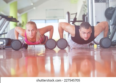 Gym man and woman push-up strength pushup with dumbbell in a fitness