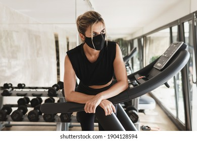 Gym new normal. Young athletic woman wearing a prevention face mask during her fitness workout.