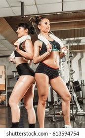 The gym on the background of trainers. People do sports to keep a slender figure. The   girl doing pullups   a group of people resting on a workout, in the hands of apples.
