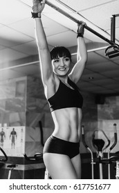 The gym on the background of trainers. People do sports to keep a slender figure. girl doing pull-UPS body parts close up, such as the abdomen, back muscles. to measure waist Size .