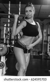 The gym on the background of trainers. People do sports to keep a slender figure. body parts close up, such as the abdomen, back muscles. to measure waist Size .