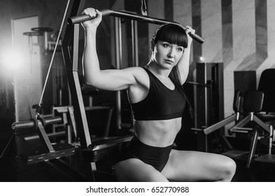The gym on the background of trainers. People do sports to keep a slender figure.  the girl tightened