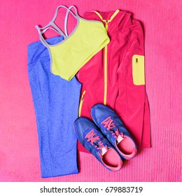 Gym outfit workout clothes on exercise yoga mat. Fitness clothing, running shoes, leggings, sports bra, top, for working out. Fashion activewear.