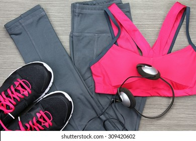 Gym outfit - workout clothing, running shoes, headphones and smartphone to listen to music while working out at the fitness center. Matching clothes, sports bra.