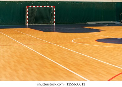 Gym for playing futsal, mini-football. Folded wooden parquet on the field of hall for mini-football. Futsal ball and bright line markings on the floor. Floor sports hall with bright lines of marking