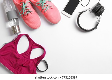 Gym stuff, mobile phone and blank space for exercise plan on white background. Flat lay composition