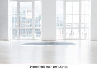 Gym white interior with black yoga mat, big windows, no people. Copy space