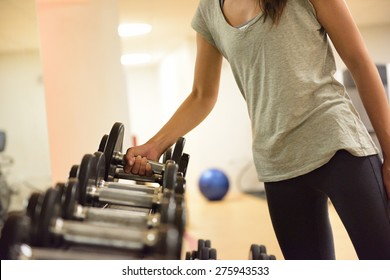 Gym woman strength training lifting dumbbell weights getting ready for exercise workout. Female fitness girl exercising indoor in fitness center. Beautiful fit mixed race Asian Caucasian model.