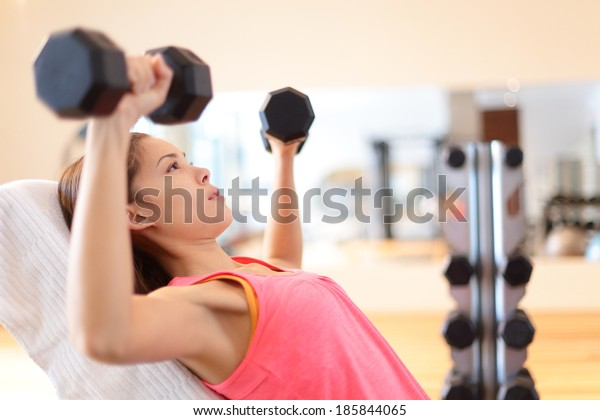 Gym woman strength training lifting dumbbell weights in shoulder press exercise. Female fitness girl exercising indoor in fitness center. Beautiful fit mixed race Asian Caucasian model training.