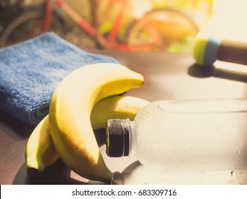 gym workout accessory close up bottle of cool drinking  water and soft focus banana , handkerchief and dumbbell background