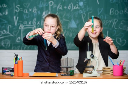 Gymnasium students with in depth study of natural sciences. School experiment. School for gifted children. Girls school uniform excited proving their hypothesis. School project investigation.