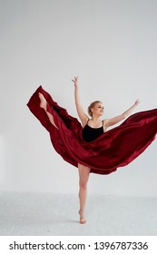 A gymnast in a dark top and a red silk skirt. The color of passion, of aggression.Tango. Plastic body, airiness , weightlessness and lightness.