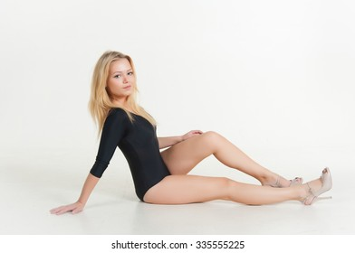 Gymnast girl with long hair in a black bathing suit
