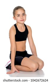 A gymnast girl prepares for the exercise. The concept of childhood and sport, a healthy lifestyle. Isolated on white background.