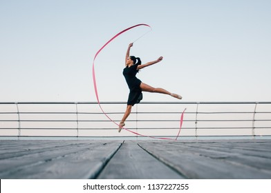 The gymnast girl splits in the air. Beautiful cool young fit gymnast woman performing an element of rhythmic gymnastics, jumping, making a jump in the air, dancing with a ribbon near the sea.