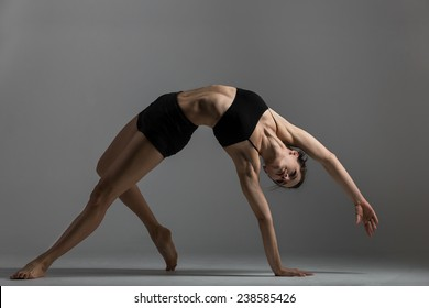 Gymnast girl is training performing exercise bridge, asana Camatkarasana, Wild Thing,  Dancing Dog yoga pose