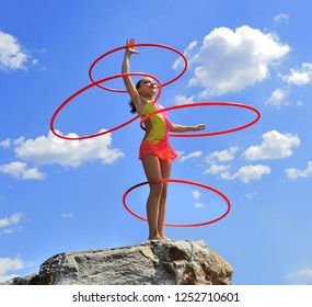 Gymnast with hoops on a background blue sky. Sports exercises in nature. Body plastics.