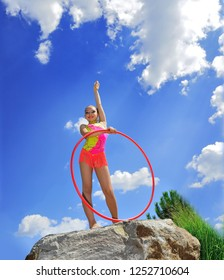 Gymnast with hoops on a background blue sky. Sports exercises in nature. Body plastics. Sports figure illuminated by the sun.