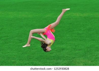 Gymnast is in a jump.Somi.Sporting exercises.Girl on a green grass.