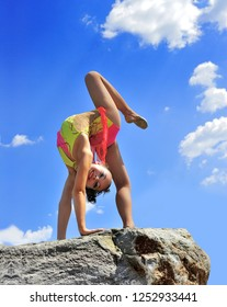 Gymnast on a rock against the sky. Sports exercises in nature. Body plastics. Sports figure illuminated by the sun.