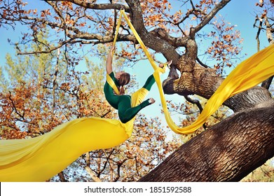 Gymnast practicing aerial silk exercises with yellow fabrics