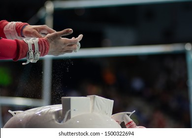 Gymnast preparing hands with magnesia before bar exercises
