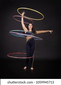 Gymnastic exercises with hula-Hoop girl performs circus performer in an artistic costume. Studio shooting on a dark background.